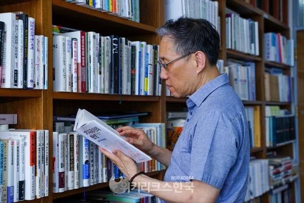 인터뷰 도중 서가에서 자신의 책을 찾아 읽고 있는 남기정 교수. [사진=최진환 기자]